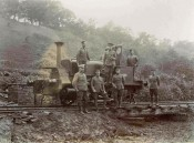 Photograph of seven soldiers in front of a small railway locomotive on a hillside, early 20th century